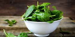 filled bowl of spinach on a table