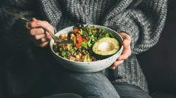 person sitting with plate of macrobiotic foods in a bowl