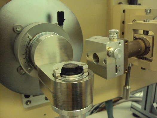 A CI chondrite being analysed by XRD. For analysis a small chip of a meteorite is powdered before being packed into a sample holder. In the image, the meteorite sample is the slightly grey region within the black sample holder. The X-rays come in from the tube at the right hand side.