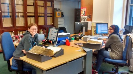 Photo of two volunteers sitting at their desks smiling at the camera