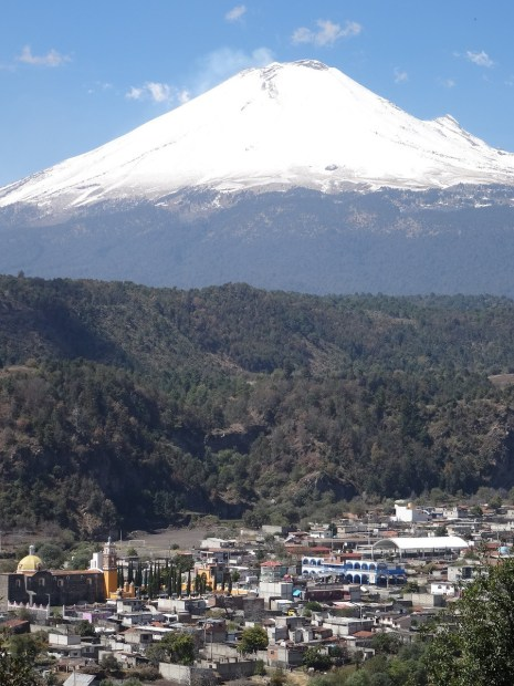 Photo showing the village close by at the bottom, with the volcano in the distance dominating top half.