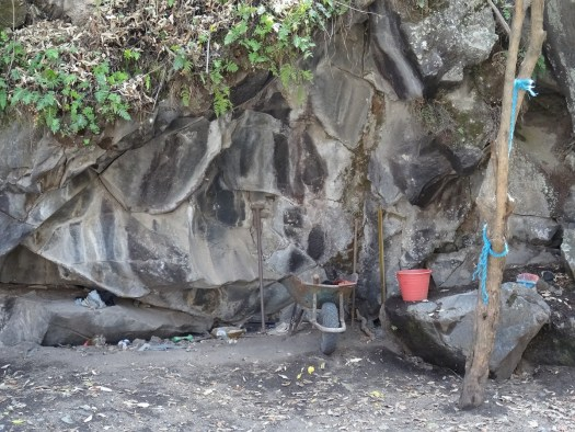 Photo showing tools and wheelbarrow resting up against a rock face
