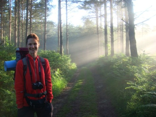 Photo of Kristina standing to the side of country lane in a wood on a misty morning