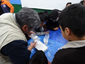 Photo showing Hugo helping a group of students pour a mould of El Popo