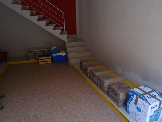 Photo of the inside of a room, with a line of sealed boxes against the wall at the bottom of a staircase.
