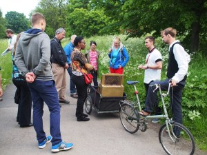 Group gather round a beehive, mounted on a bicycle trailer