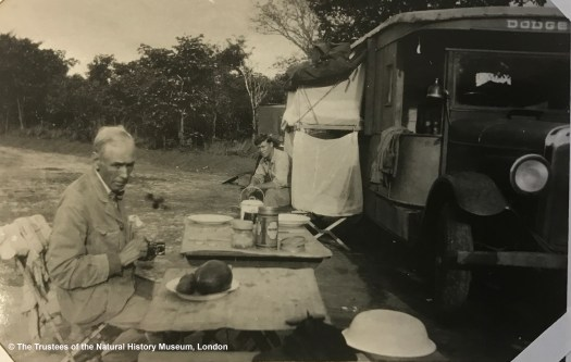 Black and white archival photograph showing a man sitting at a portable table in the foreground, a vehicle to his right and another man seated beside it to the rear.