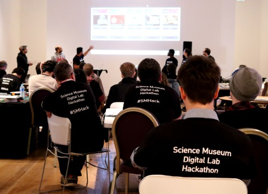 Photograph from the back of the room showing the attendees of the event seated and looking at a projection on the screen at the front of the room, with one of the teams giving their presentation.