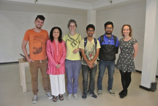 Six individuals standing in a small white room, with no windows. They are standing near to the photographer, in a line, left to right on the image, facing the camera. They different heights, gender (three male, three female) and ethnic backgrounds. All are smiling.