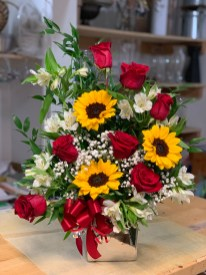 LVRE011-Red roses, sun flowers, white astromelias in a silver an elegant ceramic vaseSpecial: $80.00