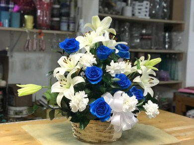 FNR023 Condolences basket with white Lillies, blue roses and cushion. $95.00