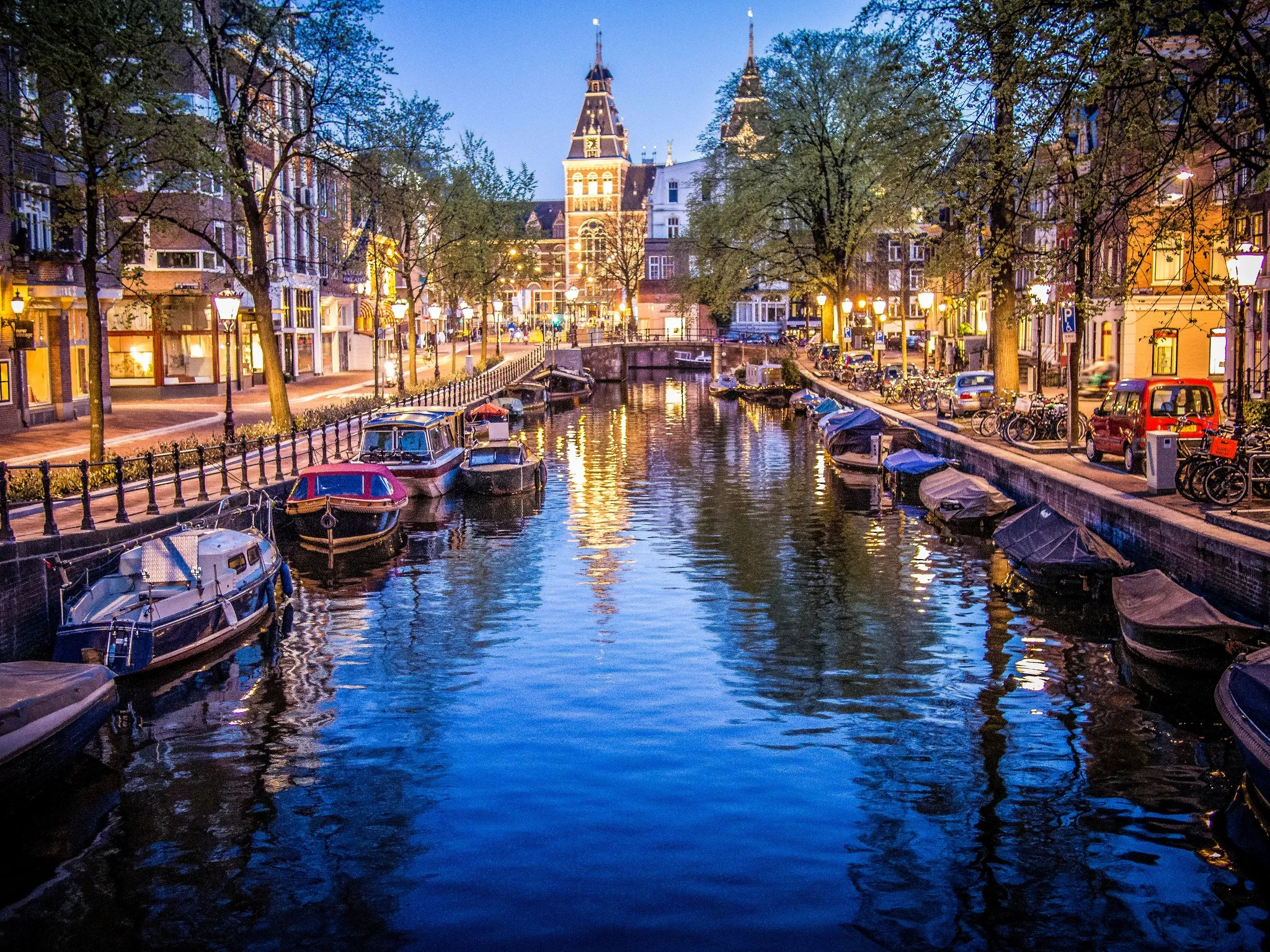 Canals and boats in Amsterdam. Photo via Flickr: Sergey Galyonkin.