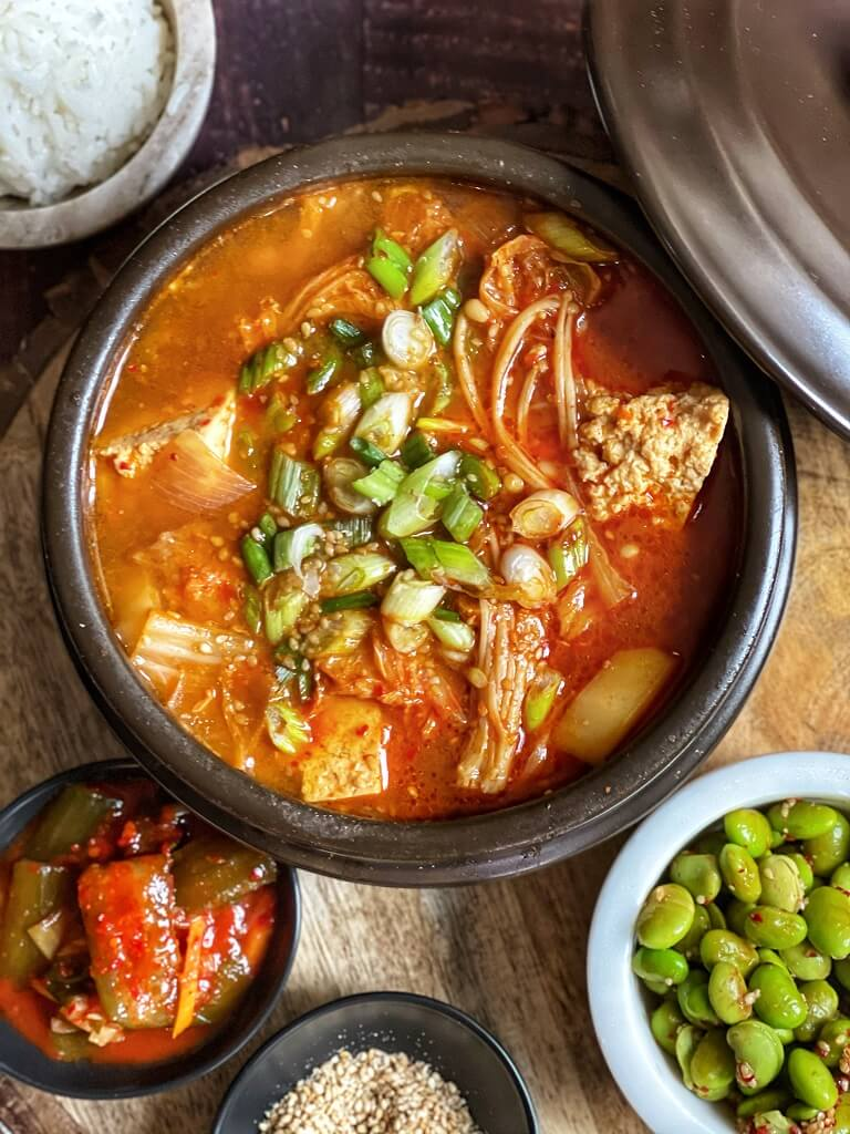 Vegan Sundubu Jjigae (Korean Soft Tofu Stew) - a hearty and comforting meal, this sizzling Korean stew features creamy tofu, enoki mushrooms, and a subtle spiceness. Try it with some rice and homemade kimchi and enjoy your favorite K-drama!