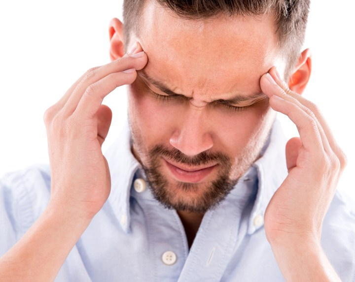 Man suffering from a headache, an early warning sign of dehydration that most people don't recognize.