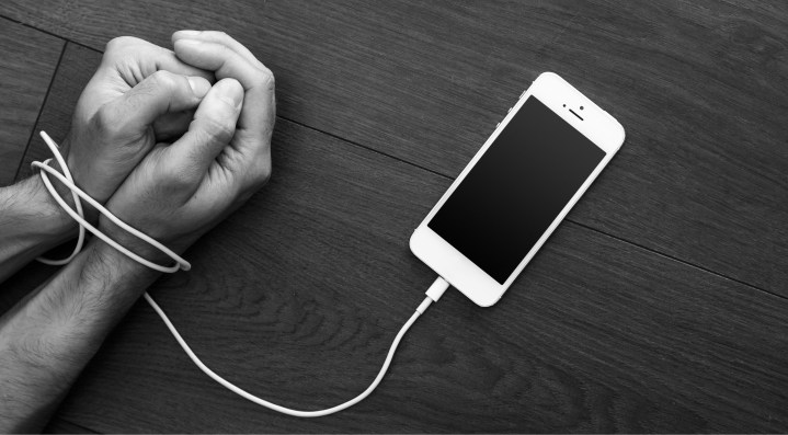 A smartphone laying on a table with the charging cord wrapped around a man's wrists.  Symbolic of the high price of your smartphone addiction.