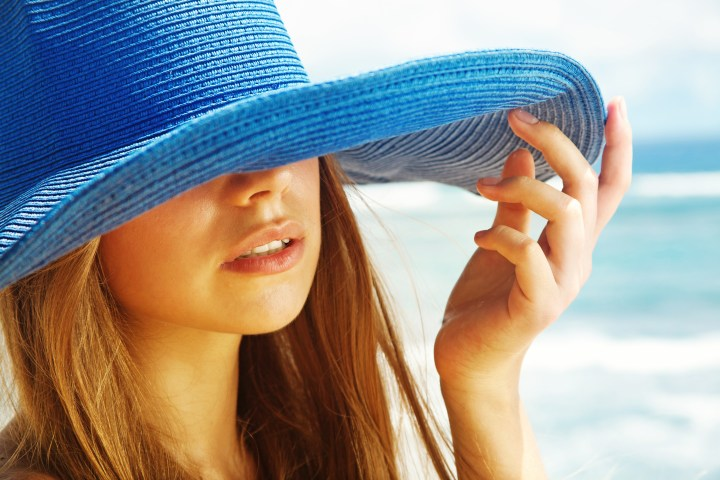 Woman at the beach wearing a hat signifying the five things to know about sun protection and skin cancer.
