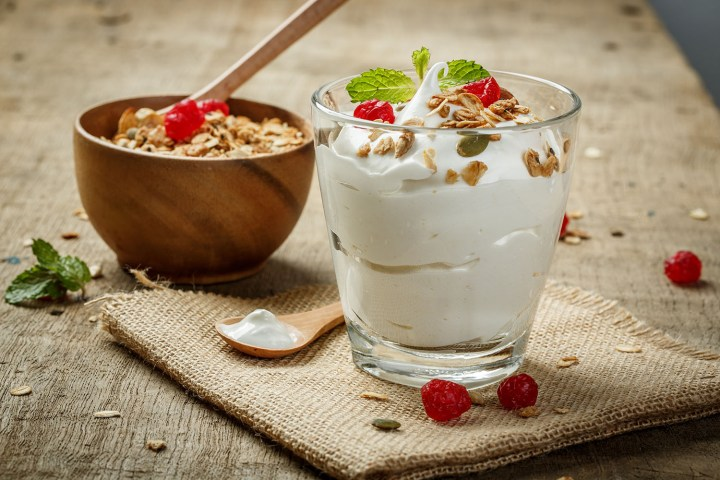 Low-fat yogurt and granola in a glass with berries and mint.