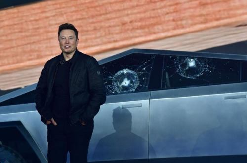 An embarrassed Elon standing in front of shattered window of the Tesla Cybertruck