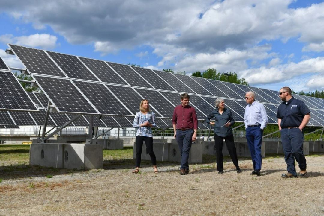 joe biden touring a solar panel plant with a group of people under a cloudy sky