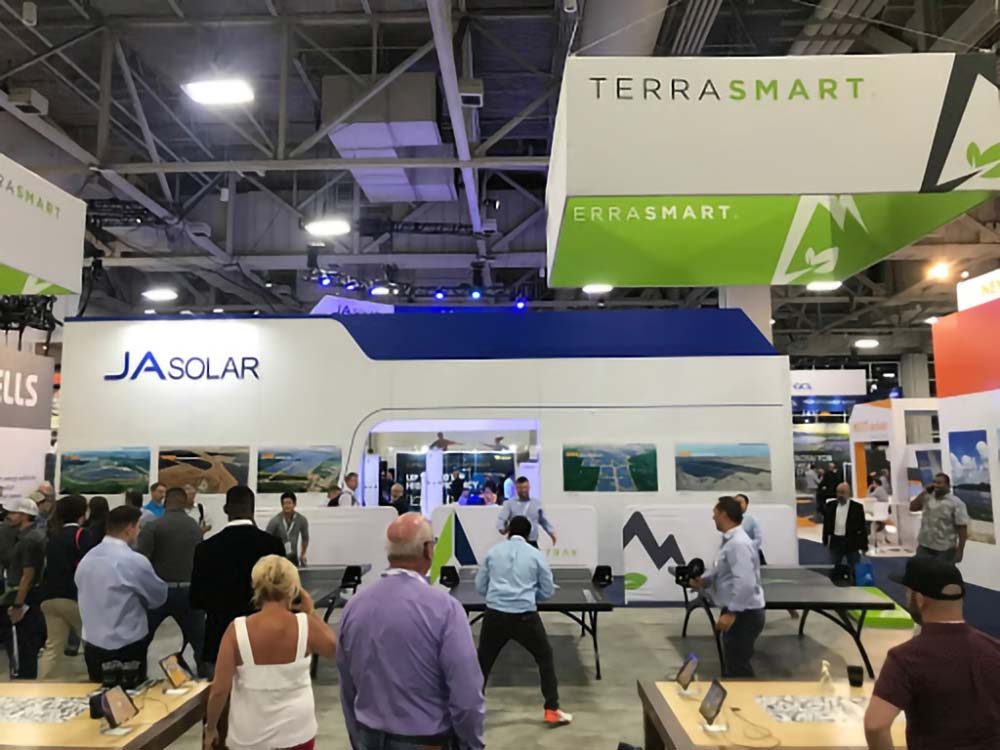 A crowd surrounds three table tennis tables in the Terra Smart booth at SPI2019.