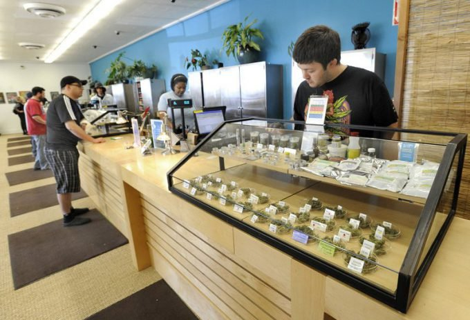 Employee Derek Flores, right, waits for a patient at a display case at the Harborside Health Center in Oakland, Calif. The center will be one of the models for Maine's first medical marijuana dispensaries. Credit: John Patriquin/Staff Photographer