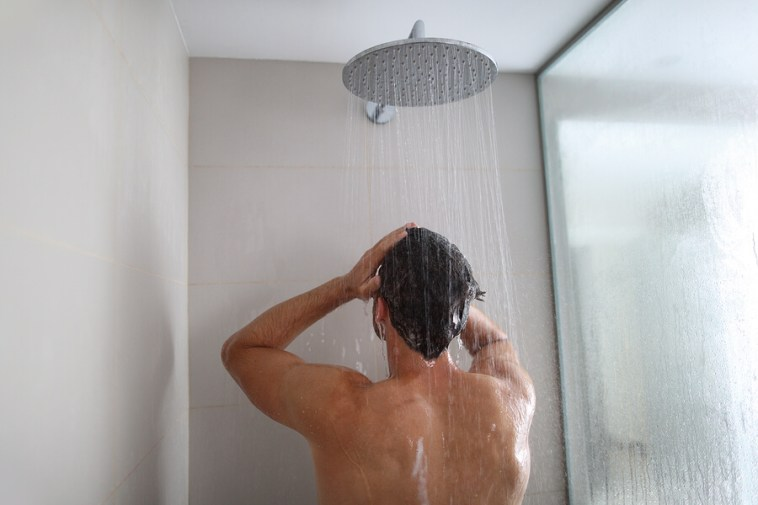 Man taking a shower washing hair under water falling from rain