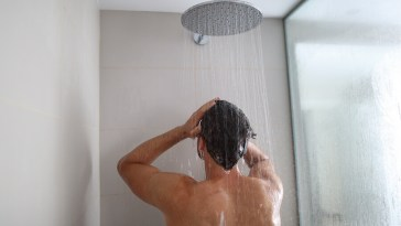 Man taking a shower washing hair under water falling from rain