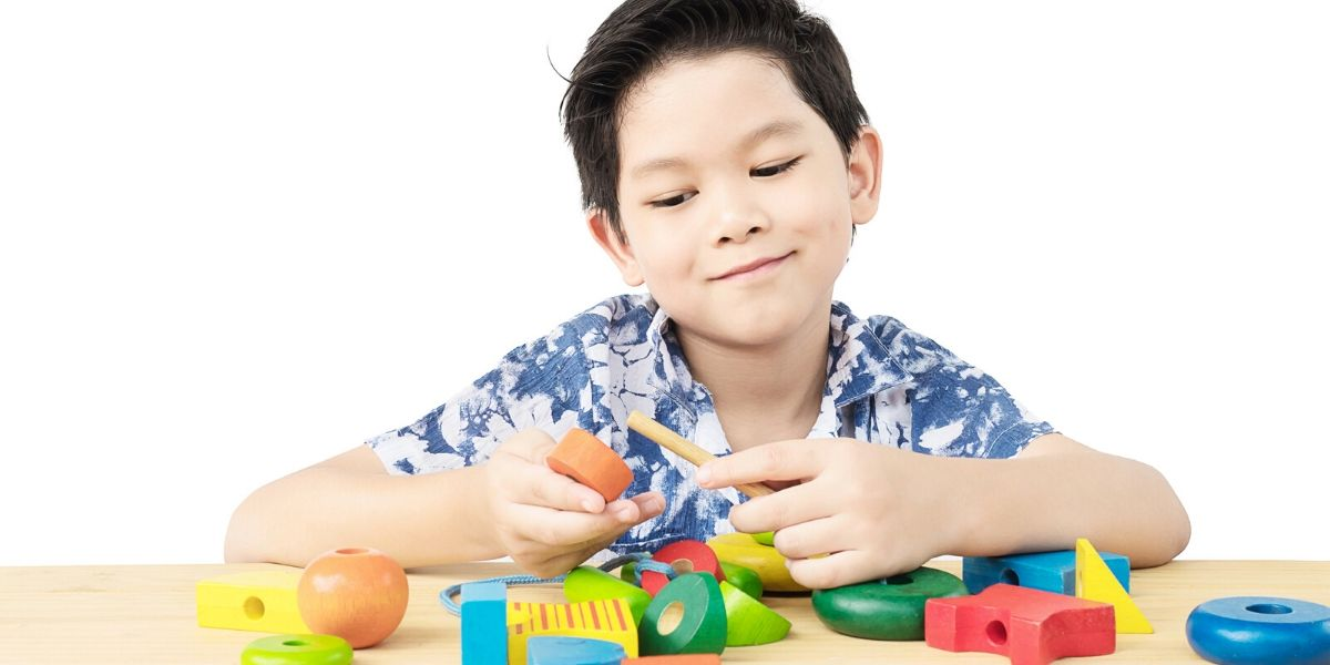 boy playing with stacking wooden toys