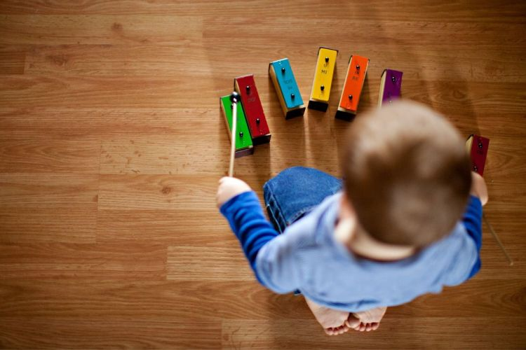 child with wooden musical toy