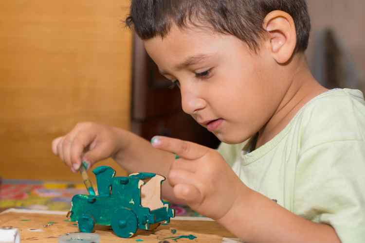 boy painting a wooden train with non-toxic paint for peg dolls