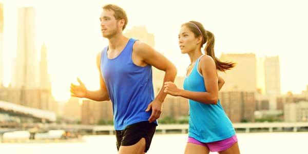 2 personnes en train de courir avec des immeubles derrière