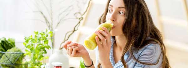 femme qui bois à la bouteille un jus de fruit vers