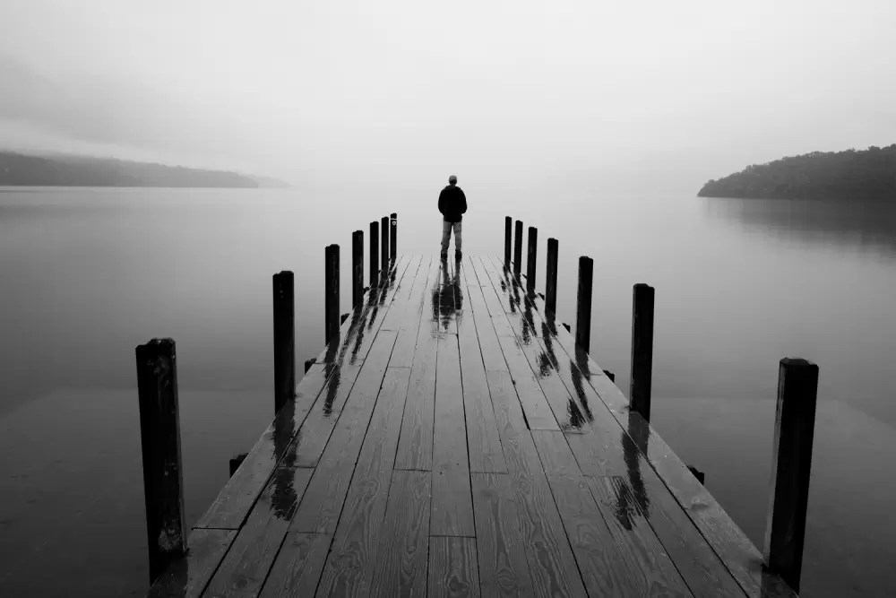 Man standing on wooden pier at Lake Rotoiti in rain; dawn MR available