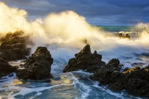 Rocky shore north of Kaikora at sunrise with dramatic storm clouds