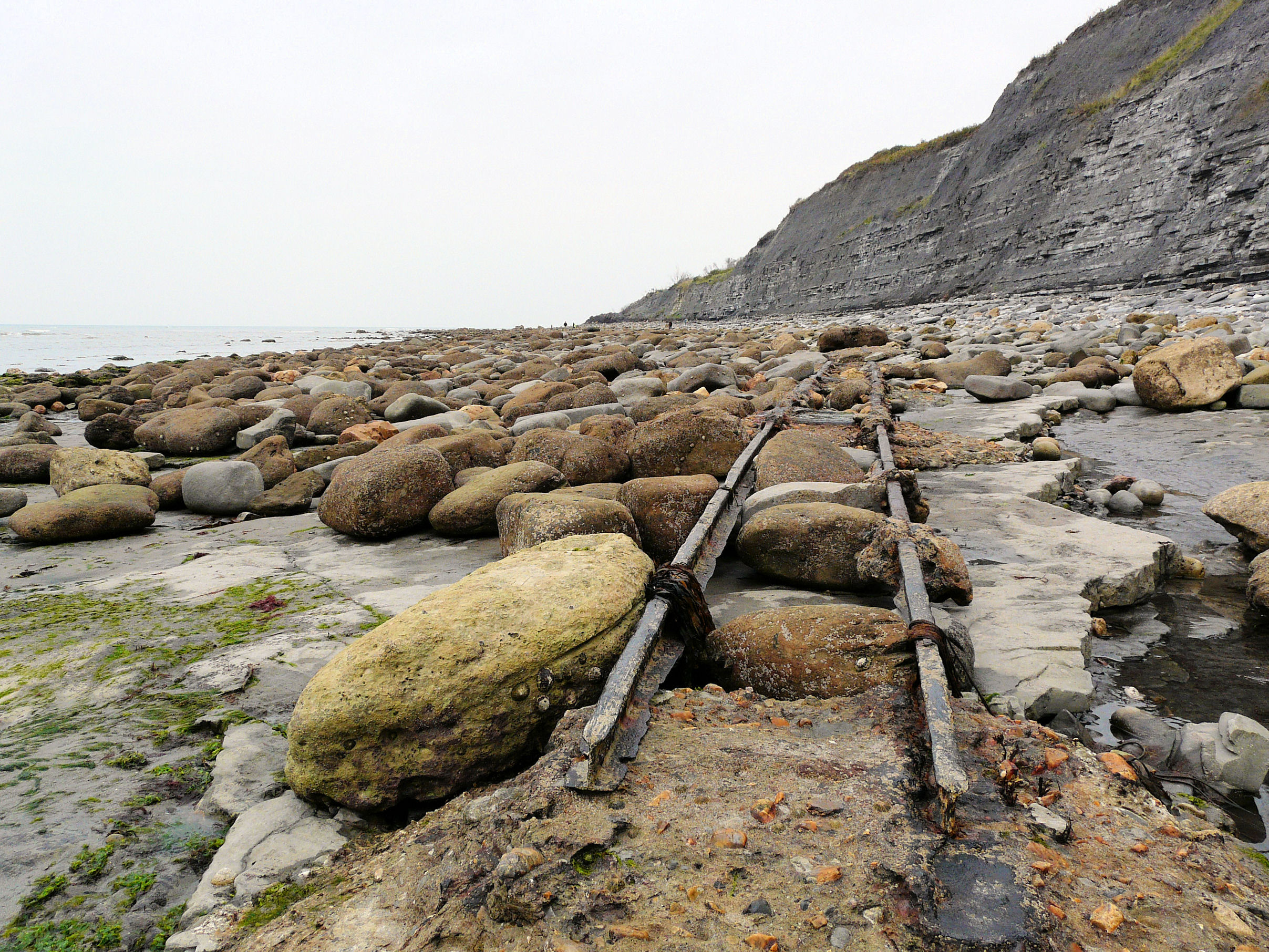 Looking westwards at old Victorian rail track and concrete seatings on Monmouth Beach, Lyme Regis, Dorset - part of the Jurassic Coast