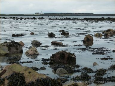 Boulders on the beach with the tide coming in