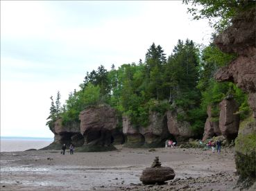 Sea stacks and red cliffs with vertical fissures and horizontal undercutting at Hopewell Rocks in New Brunswick.