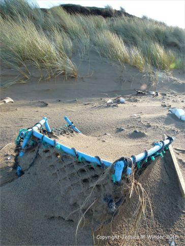 Blue plastic crate flotsam on sandy beach