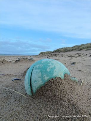 Green plastic fishing buoy washed up as flotsam