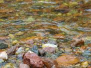 Water flowing over colourful riverbed stones at the Lone Shieling