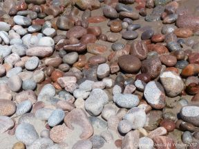 Contrasting wet and dry granite pebbles on the water's edge at Black Brook Cove