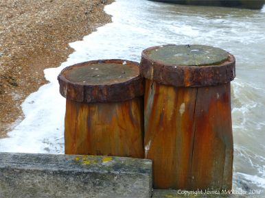 Rust-stained wooden upright post in a seashore groyne
