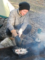 Natalia Cooking Brook Trout Wrapped in Bacon on Campfire