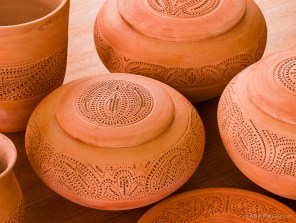 Bisque-fired and iron-oxide stained pottery