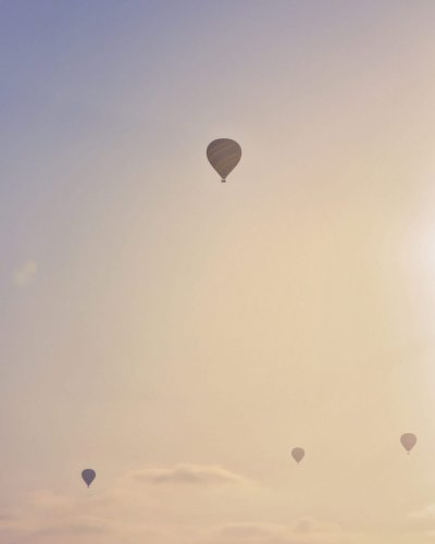 balloon photography of hot air balloons rising up in the air with blue and gold sky