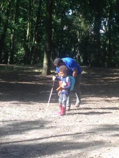 Dad litter picking nature site with child