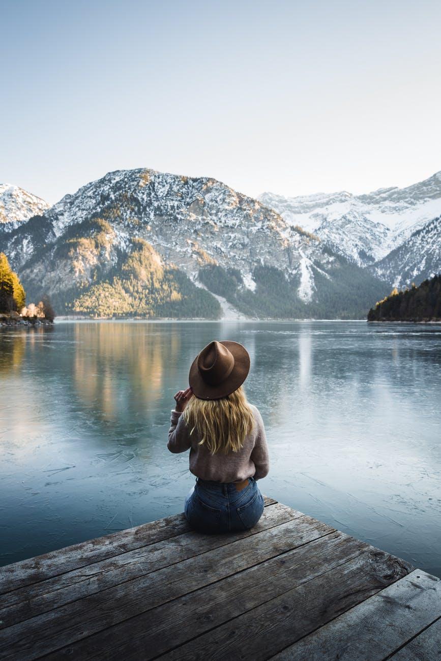woman in brown jacket sitting on wooden dock near lake