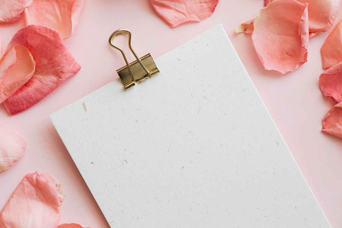 notepad with office clip among pink petals
