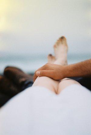 man s hand on a woman s leg
