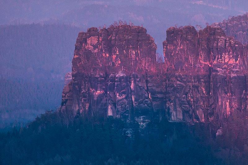 De ondergaande zon werpt zijn laatste licht op de rotsen.